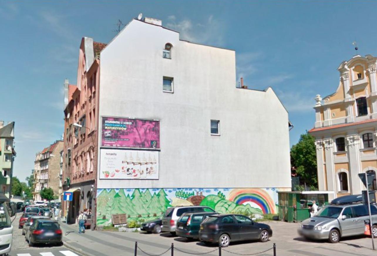 Antes: Esta fachada es blanca y un poco triste. Hay un anuncio rosa un poco feo.